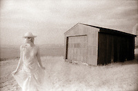 Woman standing in front of barn; sepi