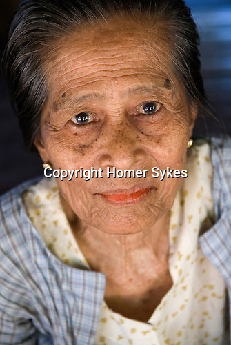 Ngwe Hsaung  older woman with betel juice on her lower lip looking like red  lipstick Burma Myanmar. .