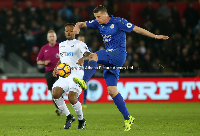 Jordan Ayew of Swansea City and Robert Huth of Leicester City contend for the aerial ball during the Premier League match between Swansea City and Leicester City at The Liberty Stadium, Swansea, Wales, UK. Sunday 12 February 2017