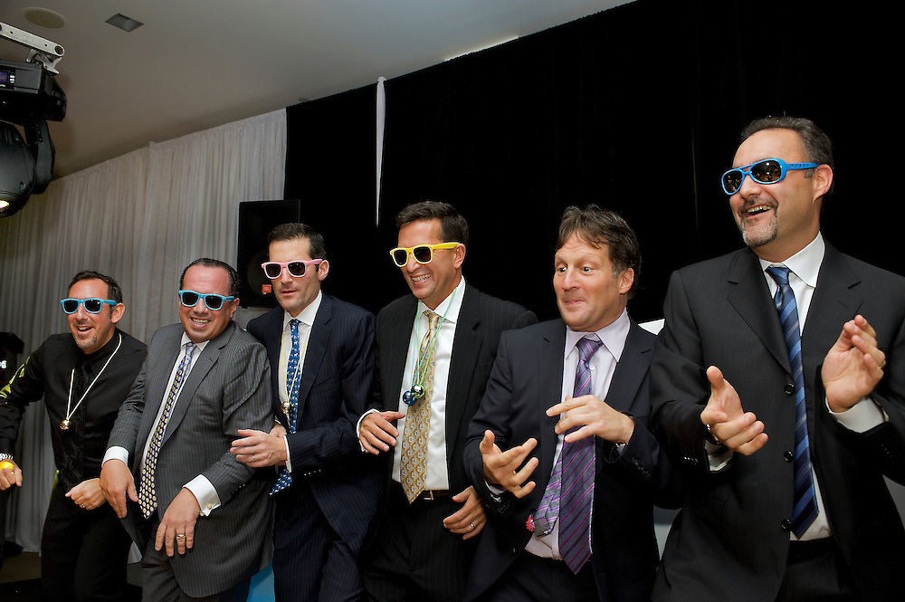 The adult guys hamming it up on stage at a Mitzvah party.