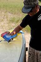 Using denatured alcohol to clean a stand up paddleboard.