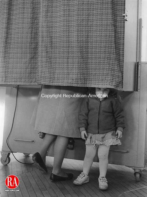 In this 1993 photo 3 1/2 year old Cali Zibluck peeks out from under the voting booth while her babysitter Jeanne Hawley votes at the Old Town Hall in Woodbury.  Republican-American Archives