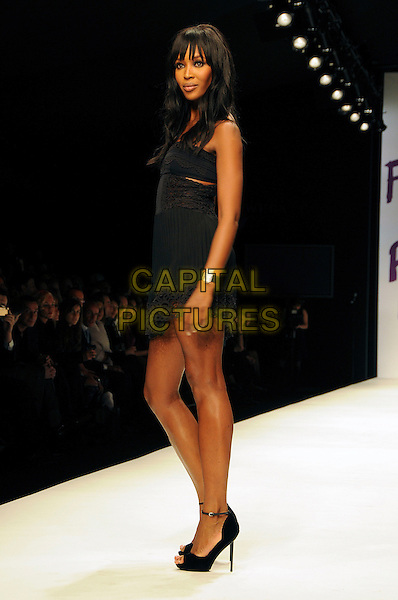 NAOMI CAMPBELL .The Fashion For Relief Haiti 2010 show for London Fashion Week Autumn/Winter 2010 at Somerset House, London, England..February 18th, 2010.LFW catwalk runway full length black dress strapless sheer lace mini side.CAP/CAS.©Bob Cass/Capital Pictures.