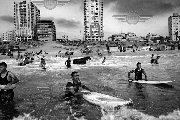 Amer Aldos (17) and Asam Abu Assi (33) enter the sea from Gaza City, as a horse stands in the water near the shore.