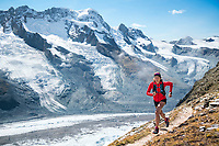 A woman trail running above Zermatt, Switzerland with the Breithorn in the background.