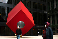 NEW YORK, NY - APRIL 20: People wearing a face masks due to COVID-19 walk near the red cube sculpture on April 20, 2020. in New York City. United States. U.S. President Trump is looking to get many Americans back to work as soon as possible, but also he recognizes that cities like New York will need to go slow. (Photo by Eduardo MunozAlvarez/VIEWpress)