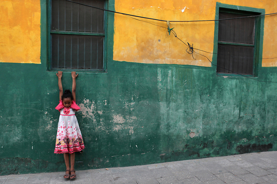 I photographed this small girl in Stone Town, Zanzibar while documenting a program that aspires to empower women through aquaculture. I was so struck by the color of the young girls' clothing against the green and yellow wall and the way in which she was hanging from the windowsill, feet just slightly off the ground, in a shy yet playful way. Having spent the previous weeks discovering how limited the opportunities for women and girls are in Zanzibar, I found her vulnerability and spiritedness particularly poignant.