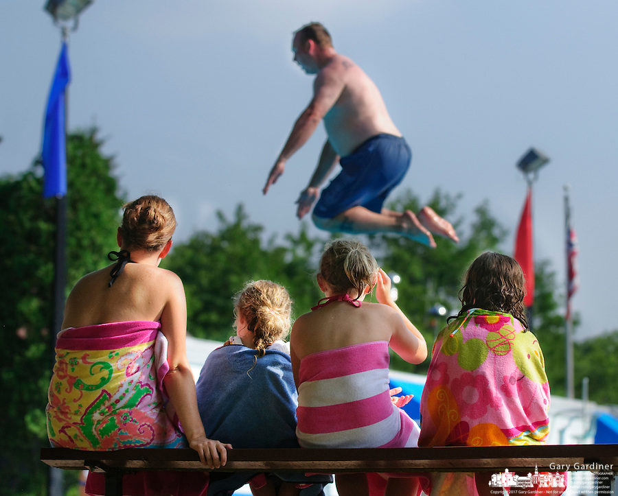 Children watch their parents and other adults use the diving pool during  an adults only period at highlands Park in Westerville, Ohio. Photo Copyright Gary Gardiner.