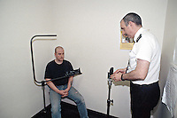 Prisoner having his photograph taken by the custody sergeant. This image may only be used to portray the subject in a positive manner..©shoutpictures.com..john@shoutpictures.com