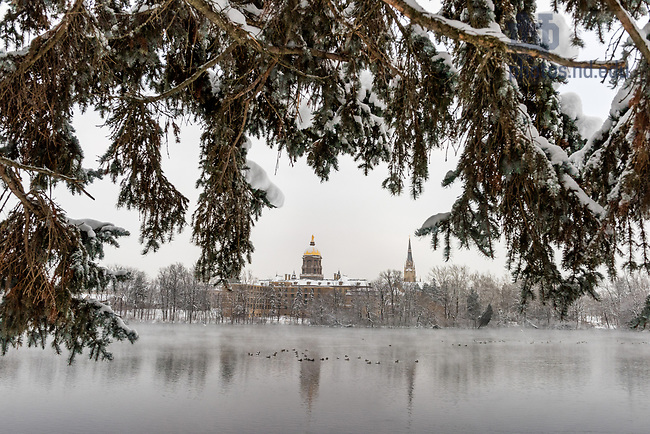 January 5, 2018; Main Building from St. Joseph Lake after snow storm. (Photo by Barbara Johnston/University of Notre Dame)