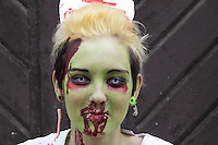 Headshot of female participant at the zombiwalks prague event may 2014. Painted green having piersings in the lips and ears and also wearing contacts. Background dark grey