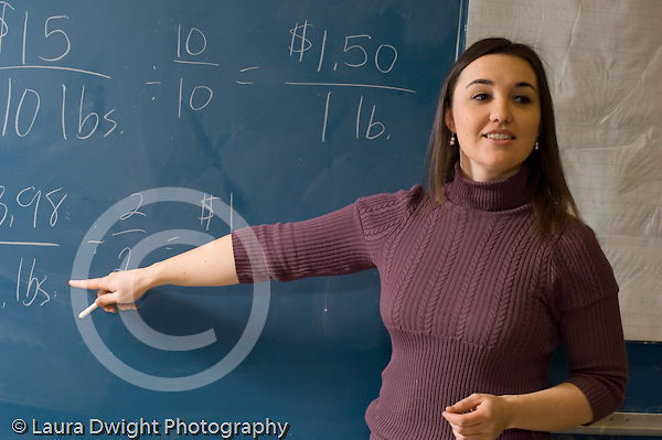 Elementary School Grade 6 female teacher explaining mathematics problem to class pointing at blackboard horizontal