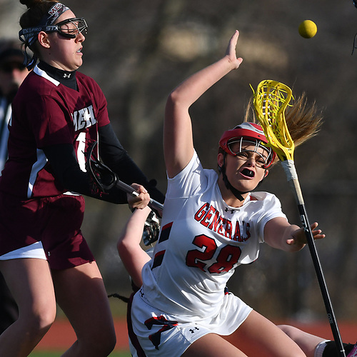 Erin Vaughan Ware #28 of MacArthur, right, draws a foul by getting to the net during a Nassau County varsity girls lacrosse game against Mepham at MacArthur High School on Monday, March 20, 2017. She tallied three goals and four assists. Her final goal drew her within one of the school's career record of 147 held by Candace Noakes. Vaughan Ware will have the opportunity to break that record during the Lady Generals' next game, which is scheduled for Saturday, March 25 10:00AM against Clarke at MacArthur High School.