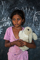 Sanya, 6, poses for a portrait with a soft toy in the Guria Non-Formal Education center in the middle of the Shivdaspur red light district, Varanasi, Uttar Pradesh, India on 20 November 2013. Guria uses the soft toys as a form of therapy for the children of the women in prostitution and also use it as signals of the children's emotional wellbeing.