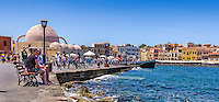 Photograph of the seaside port of Chania, Crete, Greece. This photo depicts a busy street scene of the colourful seaside port with the blue ocean in the foreground and the ancient buildings in radiating pastel colours.