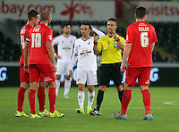 Pictured: Leon Britton of Swansea (C) watches on as match referee James Adcock speaks to L-R James Berrett, Dave Winfield and Eddie Nolan of York Tuesday 25 August 2015<br /> Re: Capital One Cup, Round Two, Swansea City v York City at the Liberty Stadium, Swansea, UK.