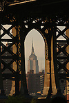 The Empire State Building seen at sunset through the structure of the Manhattan Bridge from DUMBO, New York.