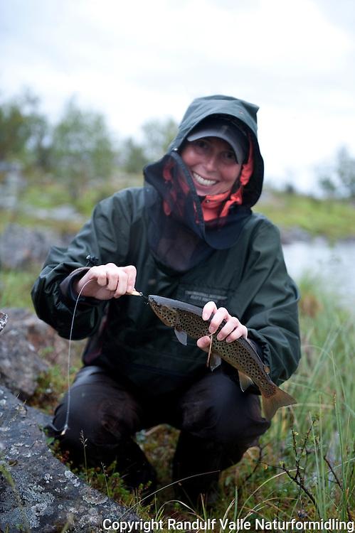 Dame har fått fin ørret på sluk. ---- Woman with trout.