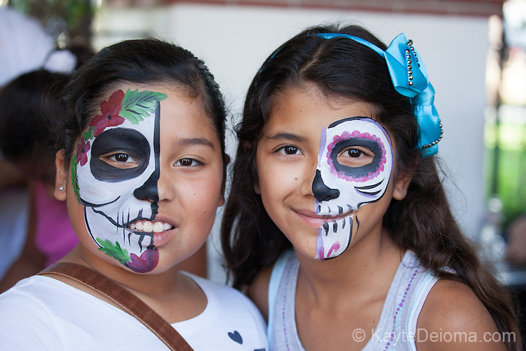Two girls with half-calavera skull face paint for Day of the Dead at the Bowers Museum in Santa Ana, CA