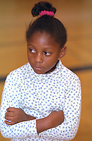 Sad girl age 6 with arms folded at Youth Express Christmas Party.  St Paul  Minnesota USA