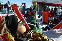 Switzerland. Valais. Crans Montana. Winter ski resort. A beautiful woman, wearing sunglasses and a scarf on her head, sits in the sun on a red plastic chair and is sunbathing on the Cry D'Er station. © 2005 Didier Ruef