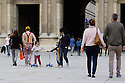 Paris, France. 09.05.2015. An eccentrically-dressed man walks past the Louvre whilst other tourists look on. Photograph © Jane Hobson.
