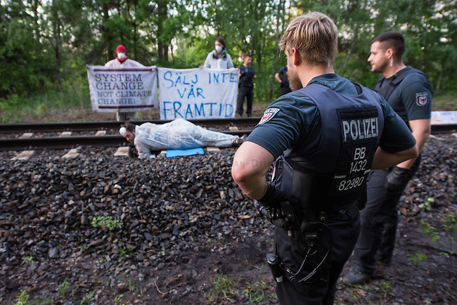 Klimacamp &quot;Ende Gelaende&quot; bei Elsterheide in der brandenburgischen Lausitz.<br /> Mehrere tausend Klimaaktivisten  aus Europa wollen zwischen dem 13. Mai und dem 16. Mai 2016 mit Aktionen den Braunkohletagebau blockieren um gegen die Nutzung fossiler Energie zu protestieren.<br /> Im Bild: Polizeibeamte beobachten Klimaaktivsten aus Schweden, Oesterreich, Finnland, und Deutschland die sich auf den Schienen einer Kohletransportstrecke angekettet haben um sie zu blockieren.<br /> 13.5.2016, Elsterheide/Brandenburg<br /> Copyright: Christian-Ditsch.de<br /> [Inhaltsveraendernde Manipulation des Fotos nur nach ausdruecklicher Genehmigung des Fotografen. Vereinbarungen ueber Abtretung von Persoenlichkeitsrechten/Model Release der abgebildeten Person/Personen liegen nicht vor. NO MODEL RELEASE! Nur fuer Redaktionelle Zwecke. Don't publish without copyright Christian-Ditsch.de, Veroeffentlichung nur mit Fotografennennung, sowie gegen Honorar, MwSt. und Beleg. Konto: I N G - D i B a, IBAN DE58500105175400192269, BIC INGDDEFFXXX, Kontakt: post@christian-ditsch.de<br /> Bei der Bearbeitung der Dateiinformationen darf die Urheberkennzeichnung in den EXIF- und  IPTC-Daten nicht entfernt werden, diese sind in digitalen Medien nach &sect;95c UrhG rechtlich geschuetzt. Der Urhebervermerk wird gemaess &sect;13 UrhG verlangt.]