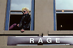 "Punk Rocker girl siiting on window ledge next to a sign that says ""Rage""  during the University District street fair along the Ave, Seattle, Washington State USA"