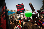 "© Licensed to London News Pictures . 03/06/2016 . Tel Aviv , Israel . Placard reading "" Homophobia and racism are both crimes of hate "" . Over 100,000 people attend the gay pride parade in Tel Aviv , reported to be the largest such event in the Middle East and Asia . The Israeli government has been accused of using the event as "" pinkwashing "" , marketing the event in order to deflect accusations of poor human rights behaviour . Photo credit: Joel Goodman/LNP"
