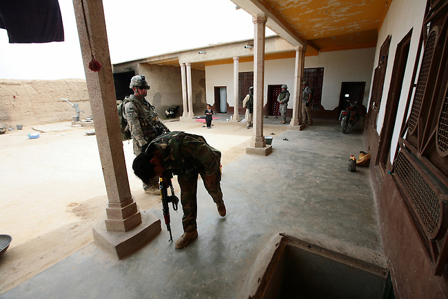 Afghan troops and U.S. soldiers with Company C, 2nd Battalion, 2nd Infantry Regiment search a compound during a patrol in the villages of Loy Kariz and Sawar Kariz in Maiwand district, Kandahar province, Afghanistan. April 9, 2009. DREW BROWN/STARS AND STRIPES