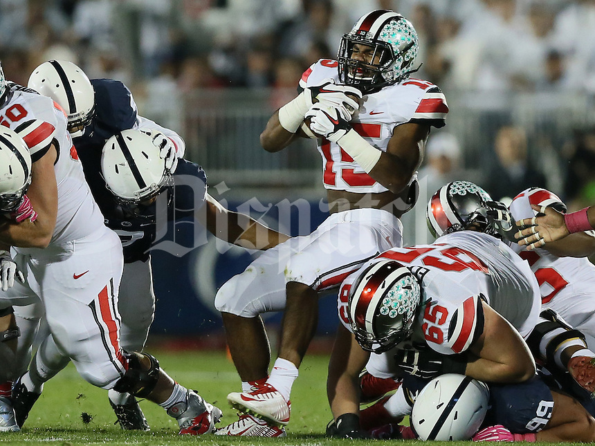 Ohio State Buckeyes running back Ezekiel Elliott (15) avoids a tackle in the first quarter of their game at Beaver Stadium in State College, PA on October 25, 2014. (Columbus Dispatch photo by Brooke LaValley)