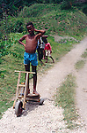 Boy with home-made wooden scooter playing in the Blue Mountains, Jamaica