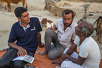 Technoserve's Field Extension Officer, Surender Singh, collects data and feedback from guar farmers Bhanwarlal Sharma, 60, and his son, Arjun Sharma, 28, at their farmhouse in Bamanwali village, Bikaner, Rajasthan, India on October 24th, 2016. Non-profit organisation Technoserve works with farmers in Bikaner, providing technical support and training, causing increased yield from implementation of good agricultural practices as well as a switch to using better grains better suited to the given climate. Photograph by Suzanne Lee for Technoserve