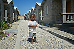 "A child stands amid houses in a model resettlement village constructed by the Lutheran World Federation in Gressier, Haiti. The settlement houses 150 families who were left homeless by the 2010 earthquake, and represents an intentional effort to ""build back better,"" creating a sustainable and democratic community."