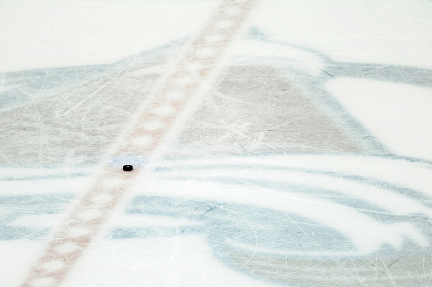 14 November 2009: A puck at center ice on top of the Colorado Avalanche logo painted under the ice during a regular season game between the Colorado Avalanche and the Vancouver Canucks at the Pepsi Center in Denver, Colorado. The Avalanche debuted their new 3rd jersey, which is blue with maroon and white striping.  *****For Editorial Use Only*****