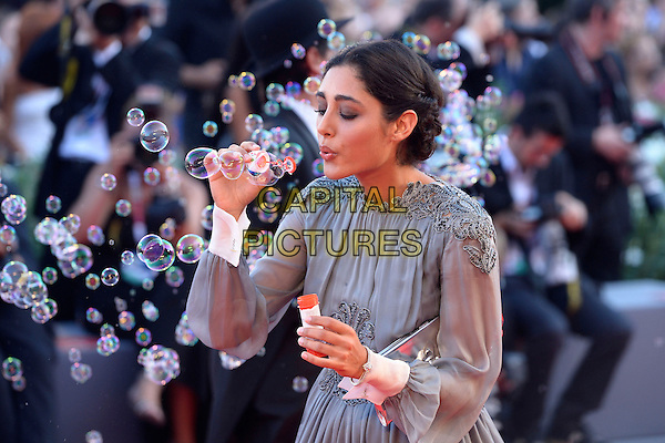 Golshifteh Farahani <br /> attending the Closing Ceremony of the 70th Venice International Film Festival at Palazzo del Cinema in Venice, Italy, September 7th 2013.<br /> half length grey gray long sleeve dress blowing bubbles clutch bag silver <br /> CAP/ZZG<br /> &copy;ZZG/Capital Pictures