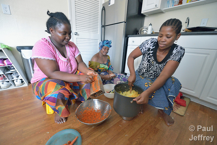 Christina Batachoka (left), Mwavita Salumu, and Eca Fitina prepare a meal on the kitchen floor of an apartment in Durham, North Carolina. The three women, all refugees from the Democratic Republic of the Congo, were resettled in Durham by Church World Service, which resettles refugees in North Carolina and throughout the United States.<br /> <br /> <br /> Photo by Paul Jeffrey for Church World Service.