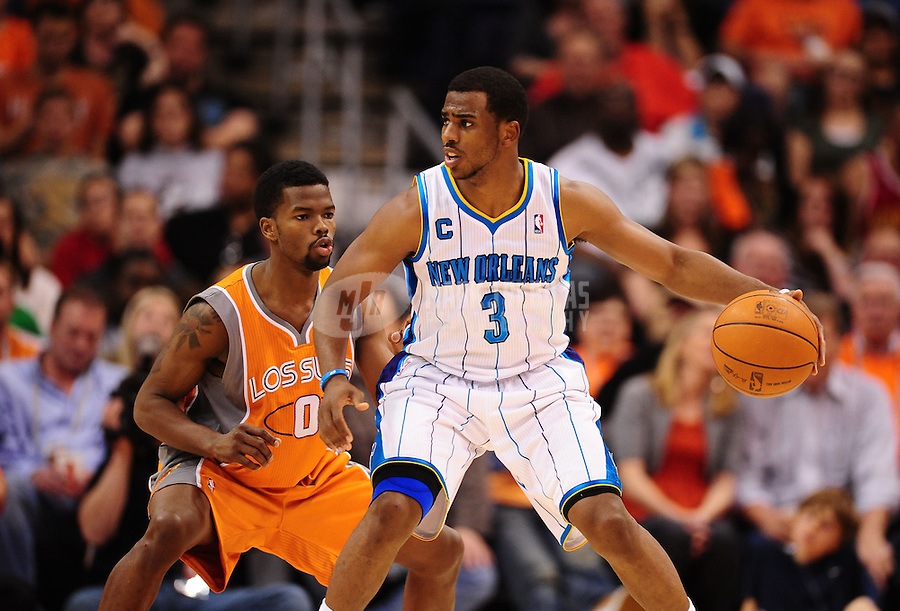 Mar. 25, 2011; Phoenix, AZ, USA; New Orleans Hornets guard (3) Chris Paul against Phoenix Suns guard (0) Aaron Brooks at the US Airways Center. The Hornets defeated the Suns 106-100. Mandatory Credit: Mark J. Rebilas-