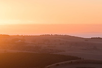 The sun sets, casting an orange glow over the Fleurieu landscape, with Kangaroo Island visible on the ocean horizon.
