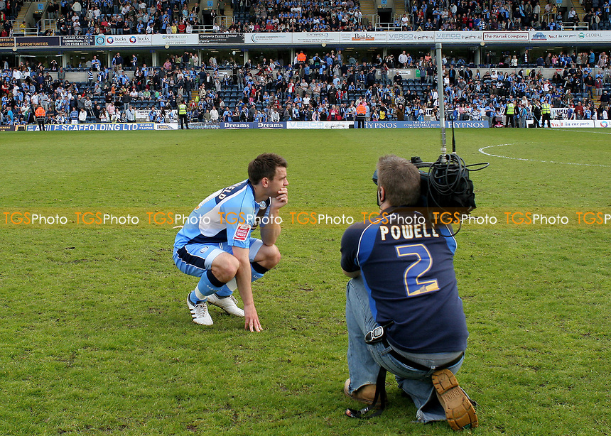 Matt Bloomfield of Wycombe Wanderers, crouches down on the pitch at the final whistle and anxiously waits to hear the results from other games to see if Wycombe have won promotion during Wycombe Wanderers vs Notts County, Coca Cola League Division Two Football at Adams Park on 2nd May 2009