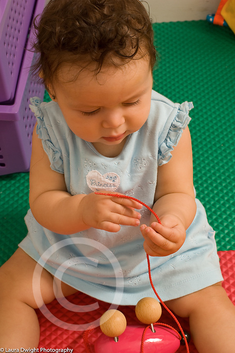9 month old baby girl sitting interested in string, cord from toy, examining it