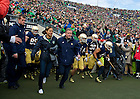 Nov. 2, 2013; Head football coach Brian Kelly runs with Cristina Bordeaux, the winner of the student lottery held at each pep rally, as he leads the football team out of the tunnel for the Navy game.<br />