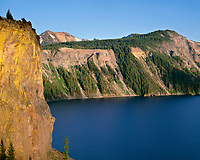 ORCL_025 - USA, Oregon, Crater Lake National Park, Evening light brightens yellow lichens on the Palisades as Mount Scott rises in the distance beyond Crater Lake.