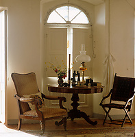 A tapestry campaign chair and a faded armchair flank a library table, on which stand a collection of binoculars and an oil lamp