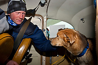 Scratched musher John Stewart pets his dog  Patriot inside the plane of Idiitarod airforce pilot Danny Davidson as they arrivein Nome from White Mountain during the 2010 Iditarod