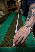 Artigiani al lavoro producono capi di abbigliamento a partire dal tweed