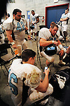 Outside a deludge of rain is pounding the stadium and in the3.locker room players wait it out while quarterback John Luster.tracks the storm on his cellphone.  The game was eventually .cancelled due to the storms.