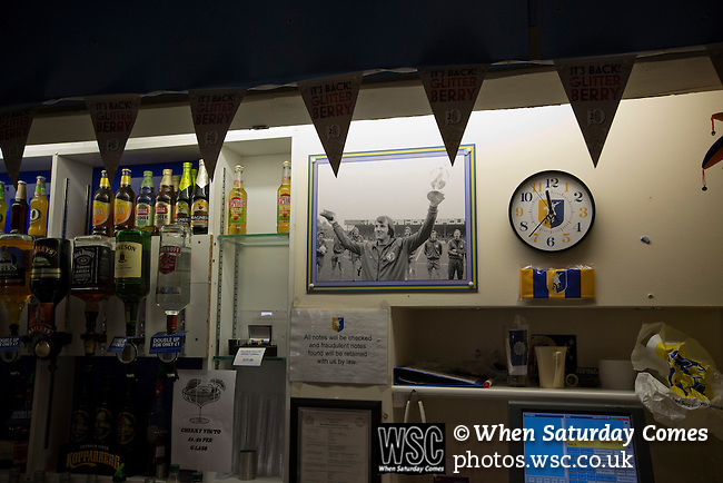 Mansfield Town Football Club Open Day, 14/07/2013. Field Mill stadium, League Two. A 1975 photo of Mansfield Town captain Sandy Pate receiving the Fourth Division trophy on display behind the bar in the Sandy Pate Lounge at Field Mill stadium during an open day held for the club's supporters. Mansfield Town achieved promotion back to England's Football League by winning the Conference National in season 2012-13. Field Mill was the oldest ground in the Football League, hosting football since 1861 although some reports date it back as far as 1850, with Mansfield Town having played there since 1919. Photo by Colin McPherson.