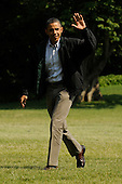 United States President Barack Obama waves while walking across the South Lawn of the White House after arriving by Marine One, in Washington DC, USA, Sunday, 10 July 2011. .Credit: Michael Reynolds / Pool via CNP