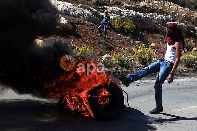 A Palestinian protester burns tires during clashes with Israeli security forces at a protest to show solidarity with al-Aqsa mosque, outside Israel's Ofer military prison near the West Bank city of Ramallah October 21, 2014. A Palestinian official on Monday called for holding an emergency Arab and Islamic summit to discuss Israeli plans to divide the Al-Aqsa Mosque compound between Jews and Muslims. In recent months, groups of Jewish settlers accompanied by Israeli security forces have repeatedly forced their way into East Jerusalem's flashpoint Al-Aqsa Mosque. Photo by Shadi Hatem